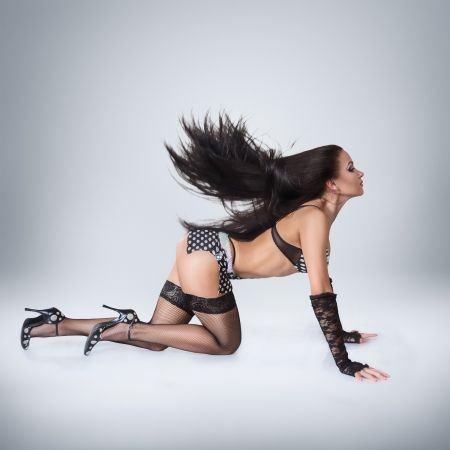 Modern style go-go dancer posing on studio against white background photo