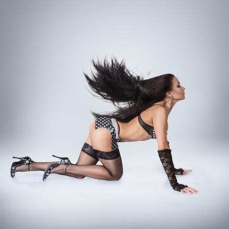 fetish wear: Modern style go-go dancer posing on studio against white background