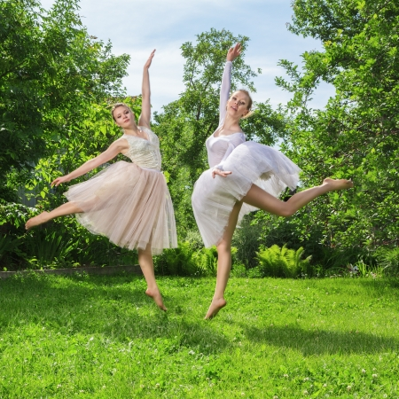 Two young happy beautiful fashion women in ballet dress jumping on green grass photo