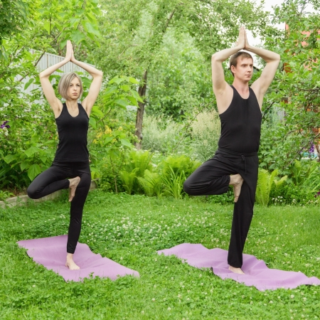 meditating: Young man and woman doing yoga  Tree pose meditation in a garden  Outdoor full body