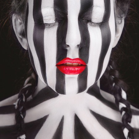 face paint: Young woman soccer fan with stripped face paint Stock Photo