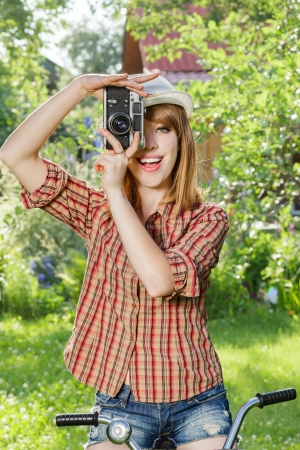 Young woman making photos with vintage film camera at summer green park. photo