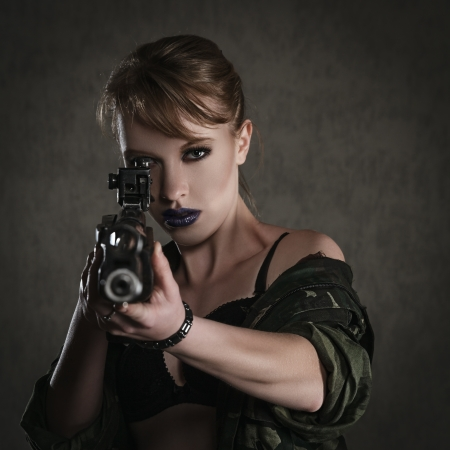 one armed: Beautiful young woman with a rifle against dark background