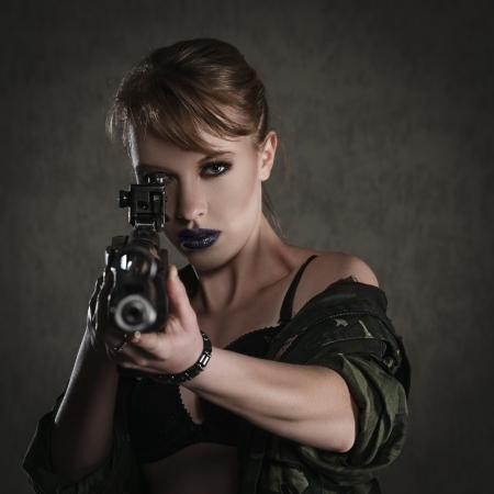rifleman: Joven y bella mujer con un rifle contra el fondo oscuro
