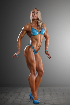 female bodybuilder: Athletic young woman posing against dark studio background
