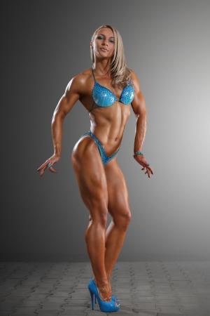 muskeltraining: Sportlich junge Frau posiert vor einem dunklen Hintergrund Studio Lizenzfreie Bilder