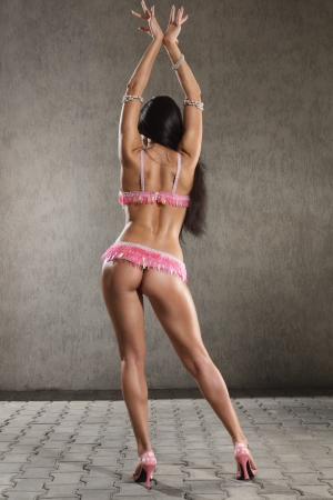 danseuse orientale: Jeune femme en costume de scène de Go-go danseuse pose sur le studio. vue arrière Banque d'images