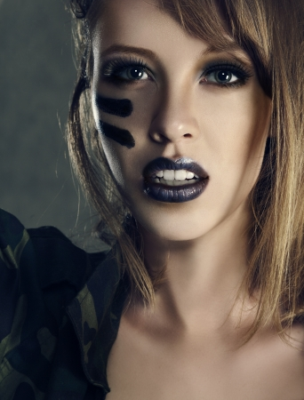 Beautiful young fashion woman with military style clothing and face paint make-up photo