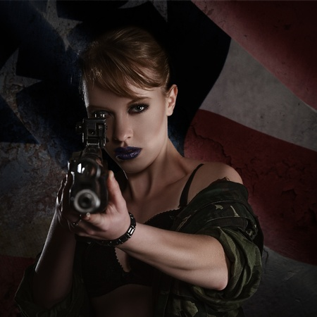 Beautiful young woman with a rifle against dark grunge american flag background photo
