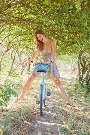 Young woman with retro bicycle in a park - outdoor portrait photo