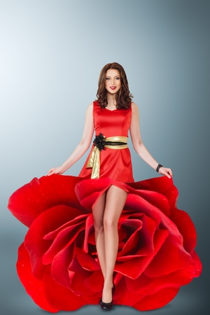 Beautiful young woman in red rose flower dress. full length studio portrait