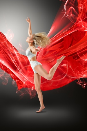 Woman in white swimwear dancing with flying fabric photo