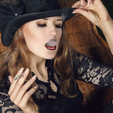 chica fumando: Joven fumar con el cigarrillo la moda posando en el jardín por la noche. Retrato al aire libre