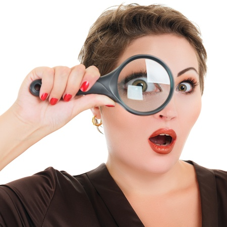 see through: Beautiful surprised woman looking through a magnifying glass isolated over white background Stock Photo