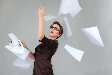 Young businesswoman throws paper document pages against light gray background photo