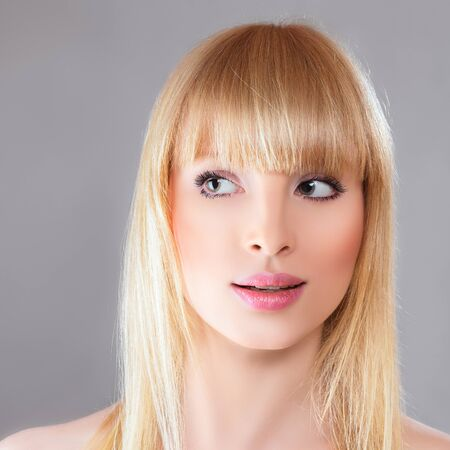 sidewards: Beauty surprised blonde woman against gray background Stock Photo
