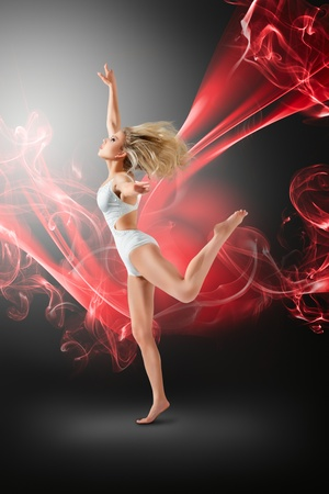 Woman in white swimwear dancing with flying fabric against dark smoky background photo