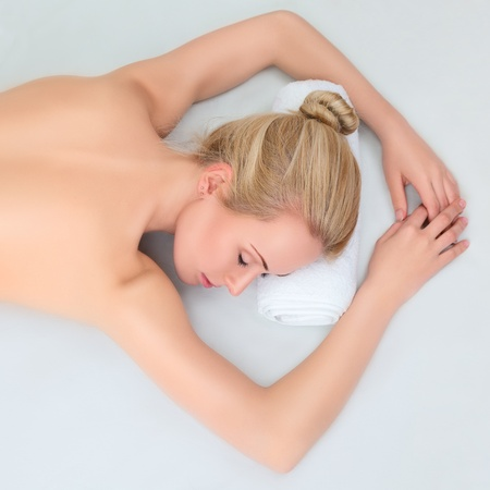 sensual massage: Young beautiful woman relaxing in health spa. Lying down. Eyes closed