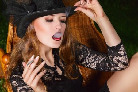 persona fumando: Joven fumar con el cigarrillo la moda posando en el jardín por la noche. Retrato al aire libre