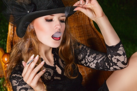sidewards: Young fashion smoking woman with cigarette posing in garden at night. Outdoor portrait