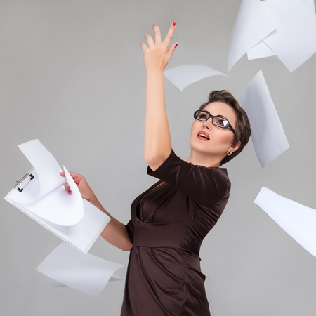 throws: Young businesswoman throws paper document pages against light gray background Stock Photo