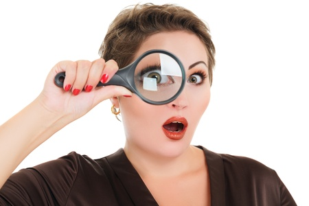 Beautiful surprised woman looking through a magnifying glass isolated over white background photo