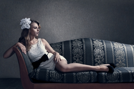 Young beautiful luxurious woman lying on a vintage couch Stock Photo - 21089588