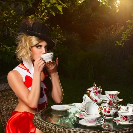 신비한 티 파티에 원더 랜드에서와 같은 웅장한 카드의 여왕 포즈 젊은 여자