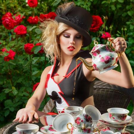 若い女性の神秘的な茶会で不思議の国からの壮大なカードの女王を装った 写真素材
