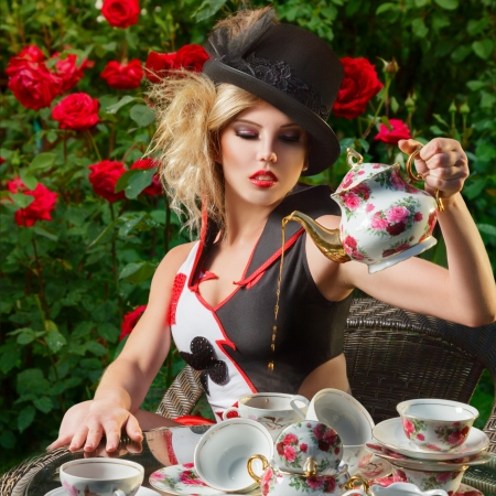 Young woman posing as magnificent card queen from wonderland at mystic tea-party Banco de Imagens