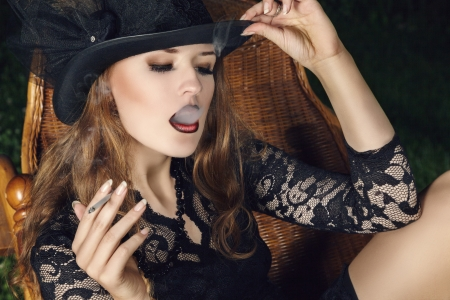 Young fashion smoking woman with cigarette posing in garden at night. Outdoor portrait