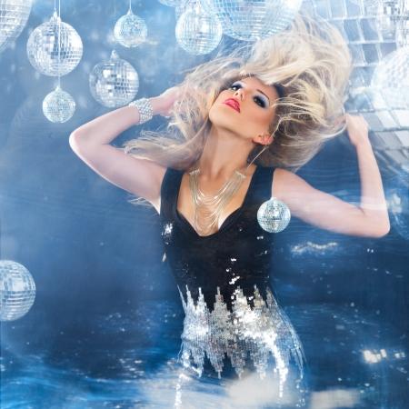 woman dancing: Young blonde woman dancing at night disco club. Motion blur