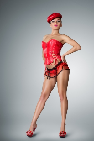 high performance: Young woman in stage costume of Go-go dancer posing on studio