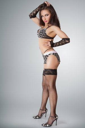 Modern style go-go dancer posing against studio background photo
