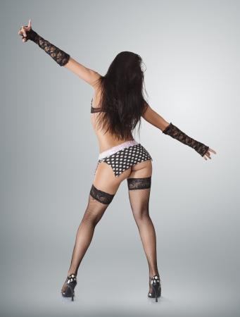 gogo girl: Moderne Go-go-Tänzerin posiert vor Studio Hintergrund. Rückansicht