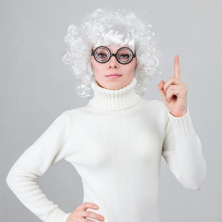 peruke: Smart woman in white wig and funny glasses have an idea against gray studio background Stock Photo