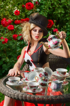 Young woman posing as magnificent card queen from wonderland at mystic tea-party Imagens