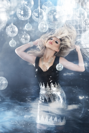 discoball: Young blonde woman dancing at night disco club. Motion blur