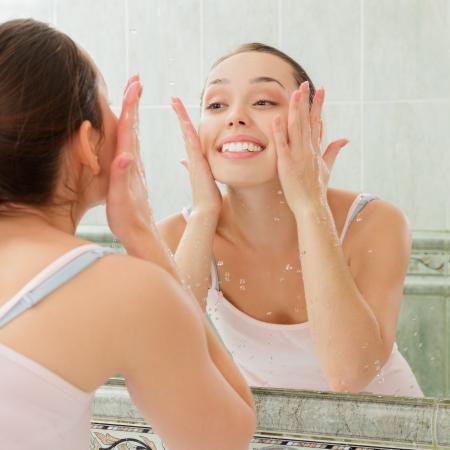 Giovane donna lavare il viso con acqua pulita in bagno Archivio Fotografico - 22036934