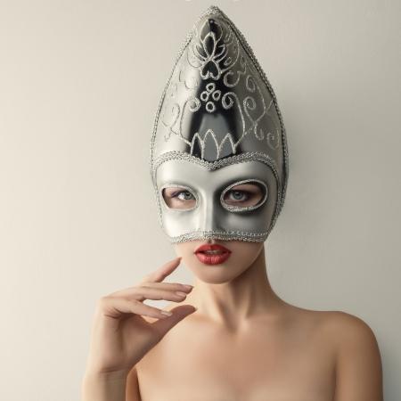 Beautiful young woman in mysterious venetian carnival mask.