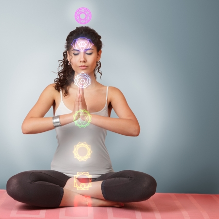 positions: Beautiful young woman doing yoga meditation in lotus position with activated chakras over body