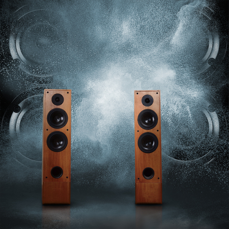 Abstract concept of powerful audio speakers blast out a cloud of dust against dark background photo