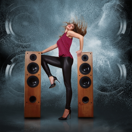 Abstract concept of powerful audio speakers blast out a cloud of dust against dark background and dancing woman posing in front of them photo