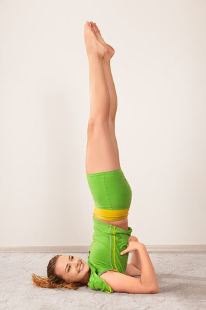lying on back: Yoga sarvangasana shoulder stand pose by young beautiful woman Stock Photo