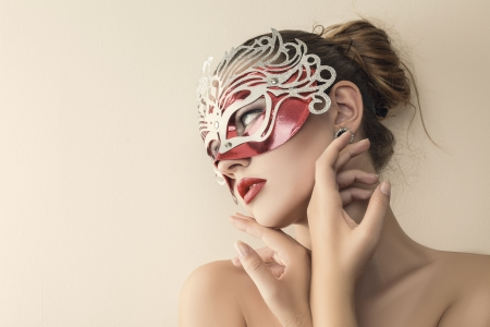 carnival mask: Beautiful young woman in mysterious venetian carnival mask. Fashion photo Stock Photo