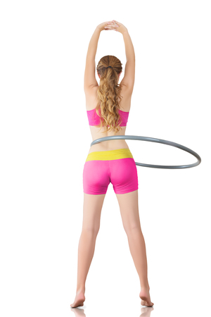 Young woman rotates hula hoop indoor background photo