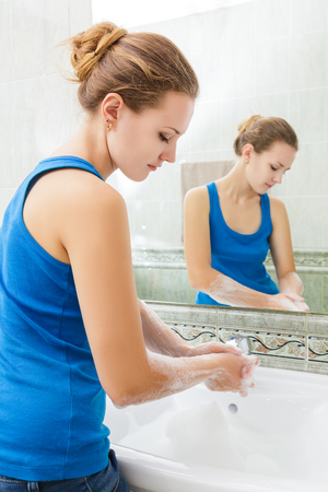 lavandose las manos: Mujer joven que se lava las manos con agua limpia y jabón en el baño