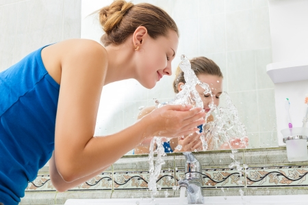 Young woman washing her face with clean water in bathroom photo