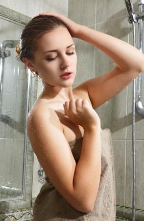 mujer bañandose: Mujer joven hermosa que toma la ducha y relajarse Foto de archivo