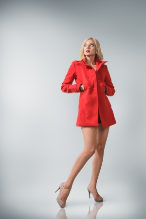 Young Fashion Blonde Woman In Red Coat Studio Portrait Stock Photo ...
